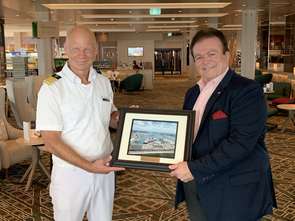 "Mein Schiff I Capt. Todd Burgman, left, receives a ceremonial plaque from  Robert ""Bobby G"" Giangrisostomi, Vice President, Cruise Business Development  with Port Canaveral earlier this month"