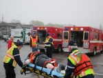 Local EMS crews load a patient into one of three ambulances